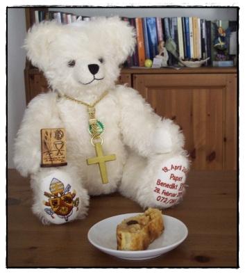 Il Papa mostra orgogliosamente i suoi regali per il compleanno: un soprammobile con contenuto spirituale e una fetta di strudel, per ricordargli la sua Germania.